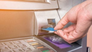 bank stocks Hand inserting ATM card into bank machine to withdraw money