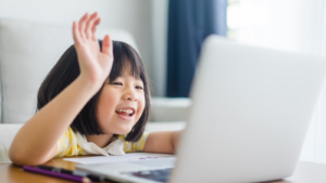 Image of a young girl raising her hand in front of a laptop.