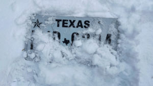 White Texas license plate obscured by snow