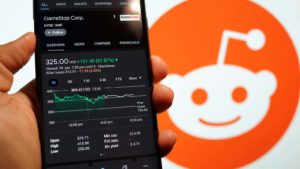 A smartphone shows GameStop (GME) up 70% with the Reddit logo in the background.