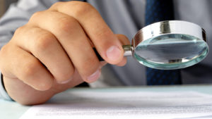 A photo of a hand holding a magnifying glass and looking at a paper.