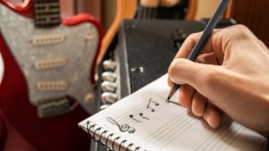 A photo of someone writing out music on staff paper with guitars in the background.