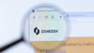 A magnifying glass zooms in on Oshkosh Corporation (OSK)'s homepage.