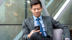 Image of a young Chinese businessman using his smartphone.