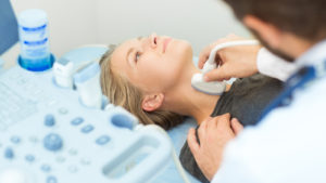A woman getting an ultrasound on her throat.
