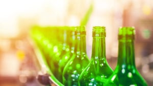 green beer bottles in a factory line, ready to be sealed. represents packaging companie
