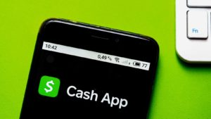 The Cash App (SQ) logo is displayed on an iPhone screen.