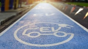 Electric vehicle logo painted on a blue street