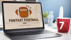 "A laptop screen shows an illustration of a football and the phrase ""Fantasy Football."""