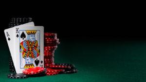 deux cartes à jouer, un as de pique et un roi de pique, appuyées contre une pile de jetons de poker noirs et rouges.  représente les actions de jeu.