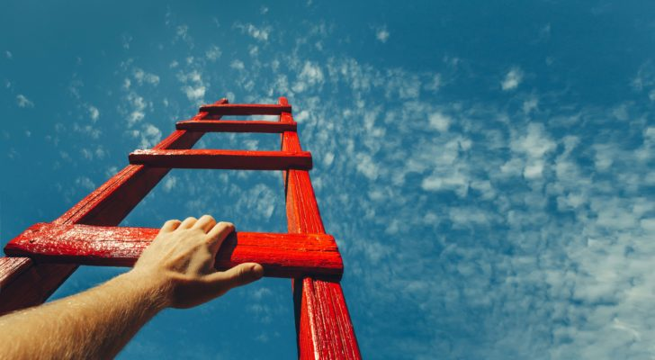 A hand reaches up on a red ladder pointing to the sky.