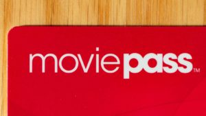 The corner of a red MoviePass (HMNY) card on a wooden surface.