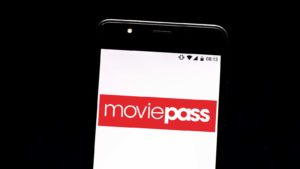 The MoviePass (HMNY) logo displayed on an iPhone screen.