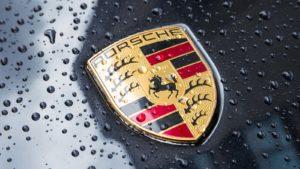 The Porsche logo on a black vehicle.