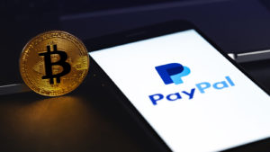 Image of the PayPal logo on a smartphone next to a physical bitcoin token.