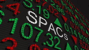 A 3D illustration of the word SPACs on a stock board full of numbers and up and down arrows.