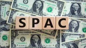 An image of wooden blocks that say SPAC over a series of one dollar bills.