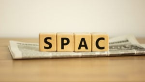 A photo of wooden blocks that say SPAC on a folded newspaper.