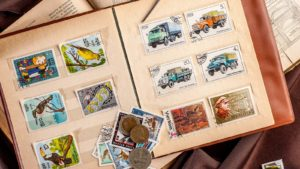 An image showing a book of collectible stamps and coins from above.