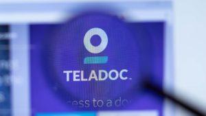 The Teladoc (TDOC) logo through a magnifying glass.