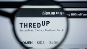 A magnifying glass zooms in on the website for ThredUp (TDUP).