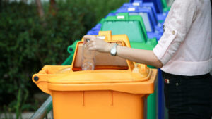person depositing a plastic water bottle in a yellow plastic recycling bin. The bin is in a line-up of several other blue and green bins.