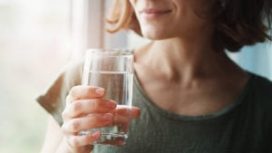 A photo of a woman holding a glass of water.