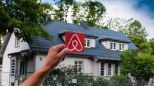 A hand holds up the Airbnb (ABNB) logo outside a home in Estonia.