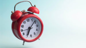 A red old-fashioned clock stands on one leg.