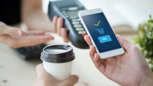 A concept image of mobile payment with a smart phone for a cup of coffee.