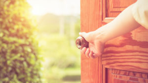 hand opening a wooden door to the outdoors. represents economic reopening