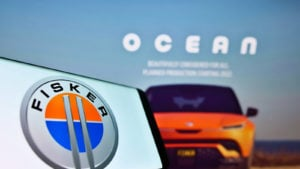 Mobile phone with company logo of US electric vehicle manufacturer Fisker Inc. on screen in front of webpage