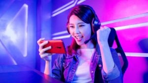A mobile gamer cheering on her smartphone with neon background.