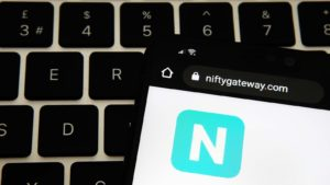 The logo for Nifty Gateway is displayed on a smartphone that rests on a laptop keyboard.
