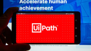 The UiPath logo on a smartphone in front of a computer screen.