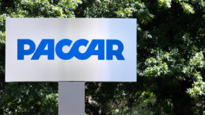 A sign for Paccar (PCAR) in front of greenery.