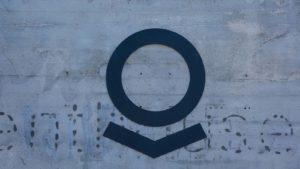 The Palantir (PLTR) logo on a grey wall.