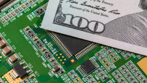 A $100 bill resting on top of a computer motherboard, a technology usually produced with rare earth metals