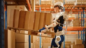 Worker Wearing Advanced Full Body Powered exoskeleton, Lifts Heavy Pallet full of Cardboard Boxes