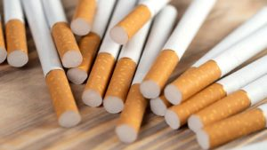 A pile of unsmoked cigarettes on a wooden background.