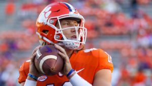 A close-up shot of Trevor Lawrence in an orange and white uniform holding a football.