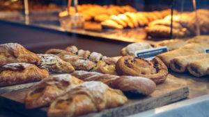 Pains de boulangerie, petits pains et pâtisseries sur une planche à découper en bois dans une vitrine