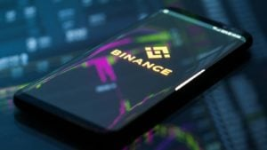 The Binance logo on a smartphone with a neon chart in the background.