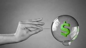 black and white photo graphic of hand holding a pin up close to a floating bubble. The bubble has a green dollar sign inside of it.