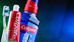 Colgate toothpaste and mouthwash in a cup with a toothbrush