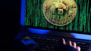 A hacker sits in front of a laptop with the concept of stealing crypto information.