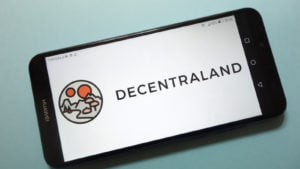 Decentraland logo displayed on smartphone screen, teal background behind the phone