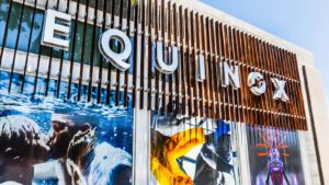 A close-up photo of an Equinox sign with colorful posters on the windows.