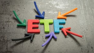 """Colorful arrows pointing at the multicolored word """"ETF"""" against a cement surface"""