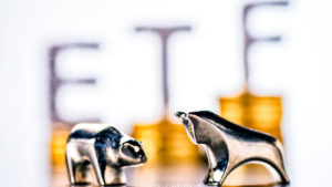 """Photo of silver bull and bear figurines with the word """"ETF"""" on top of gold coins out of focus in the background"""